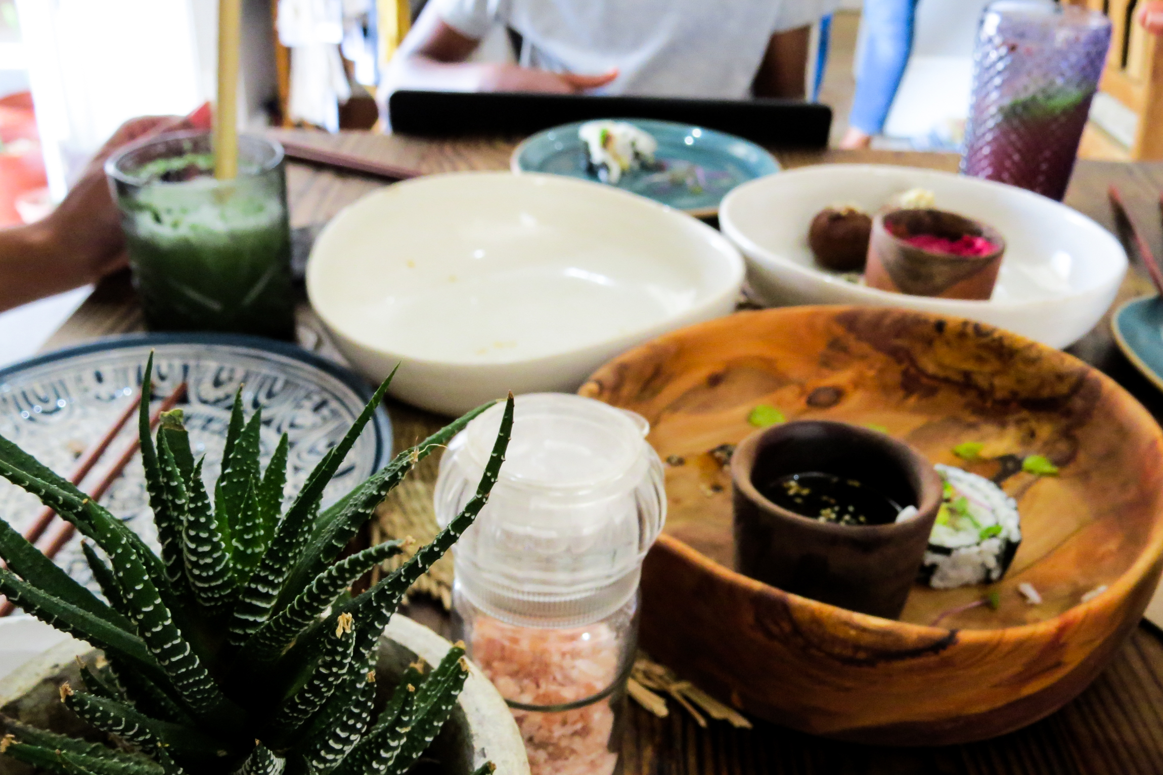 wooden bowl at restaurant table with salt and plant