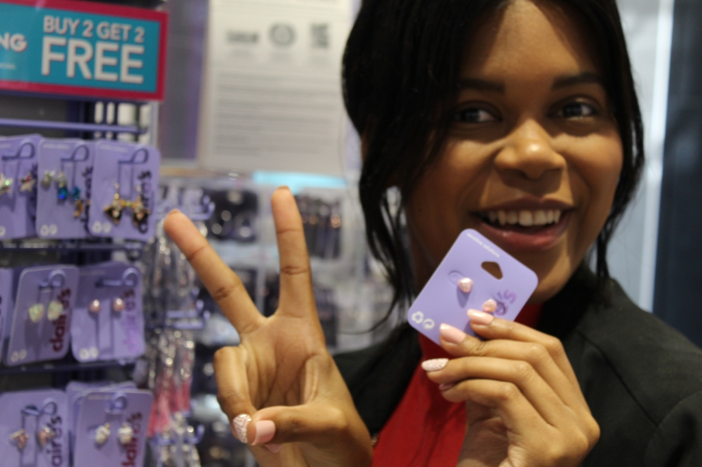 showing a peace sign while shopping for earrings at Claire's