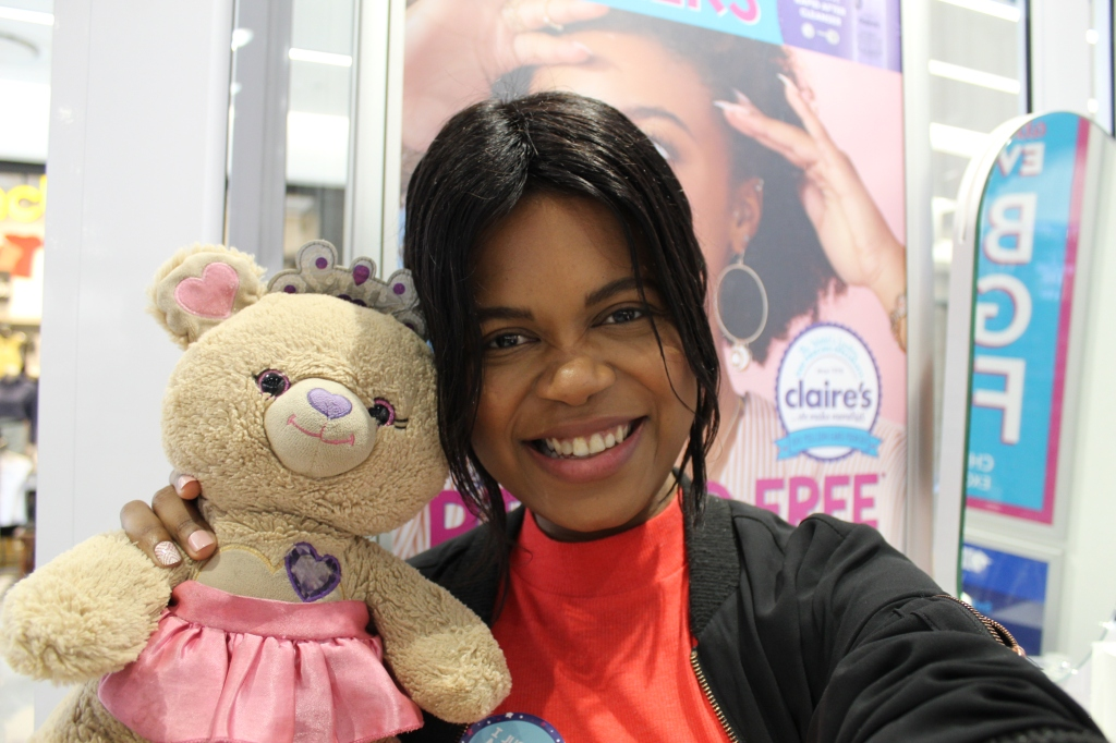 girl holding a teddy bear while after getting an ear piercing at Claire's