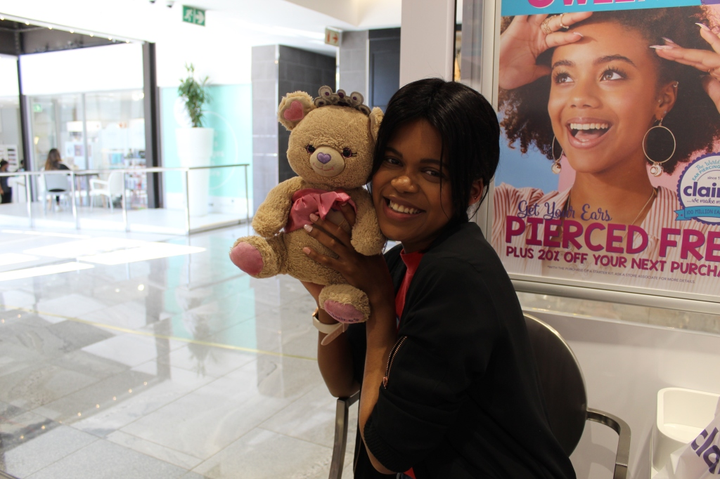 smiling girl holding a teddy bear after getting an ear piercing at Claire's