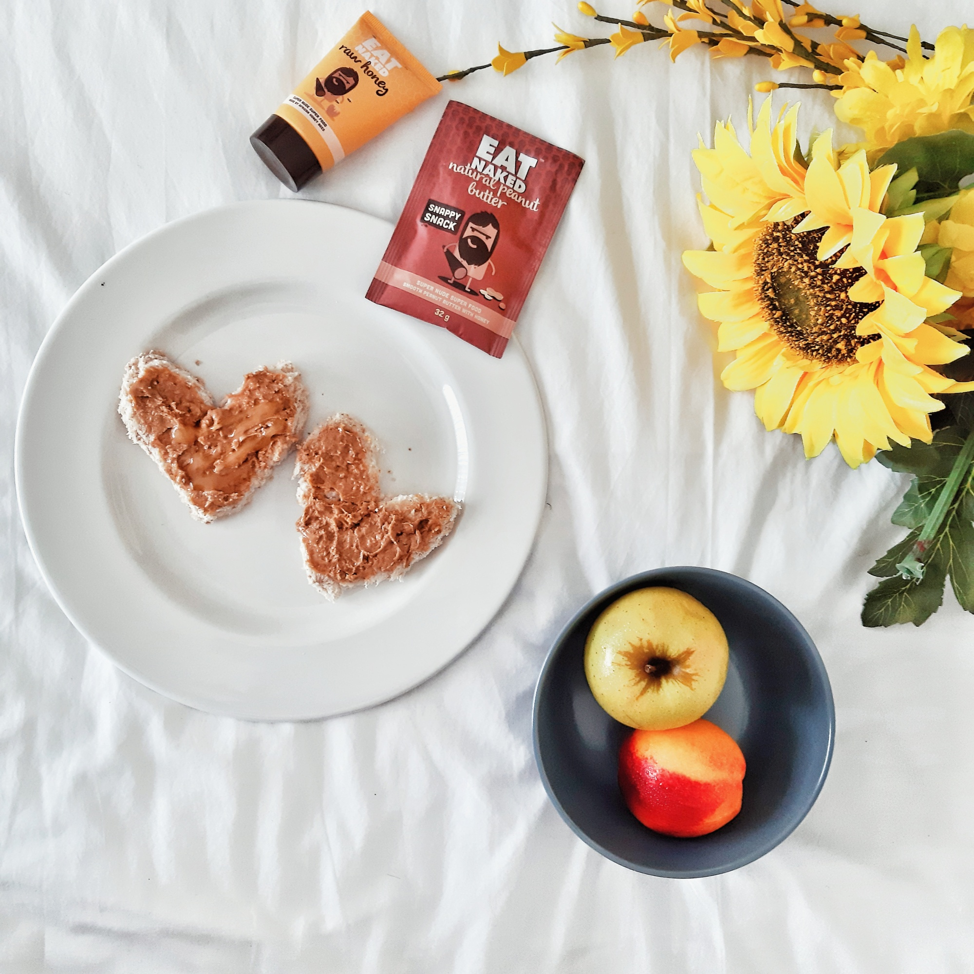 flatlay with sunflowers and fruit in a bowl and bread