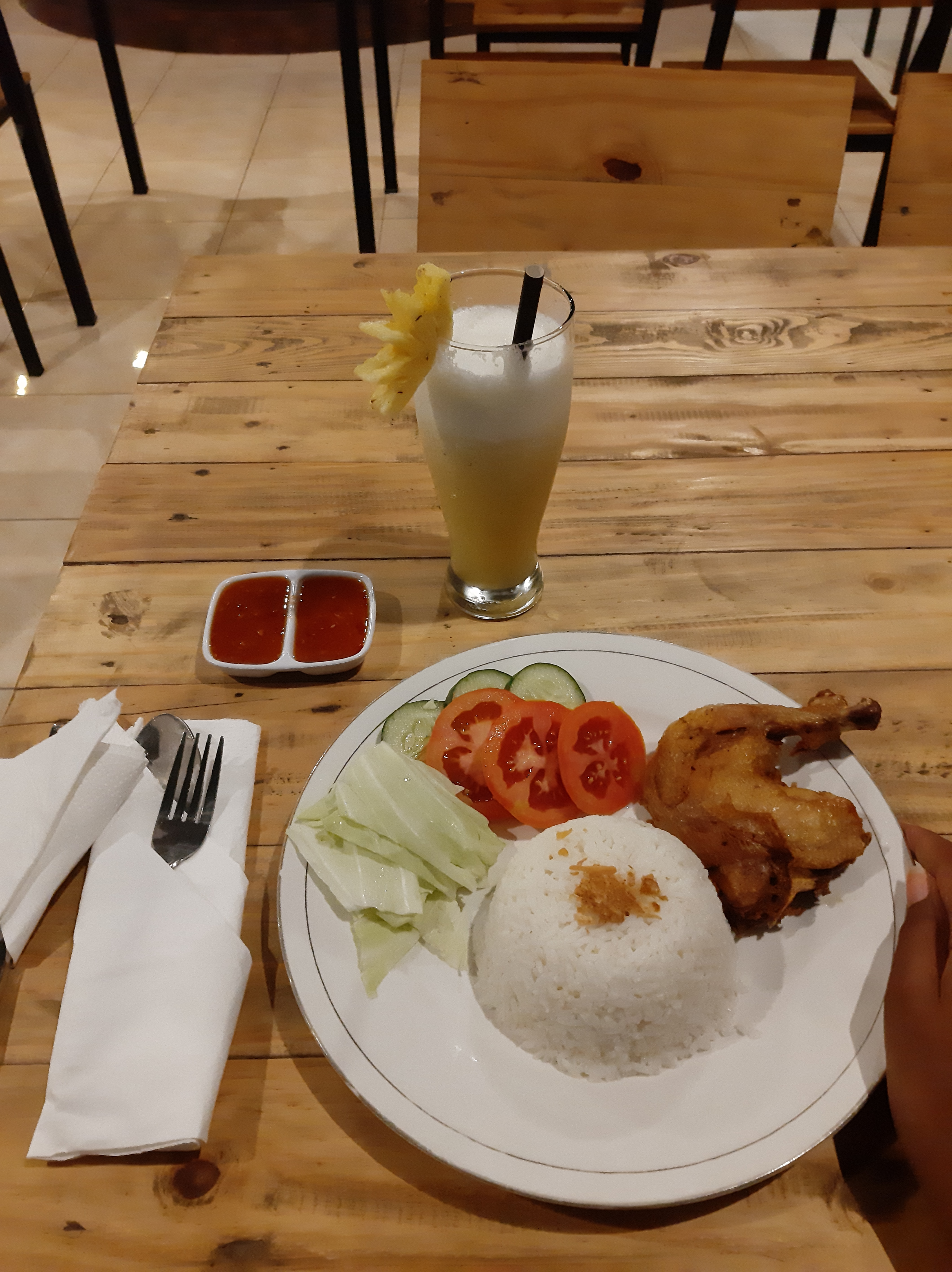 fried chicken meal with rice and tomato and pineapple juice
