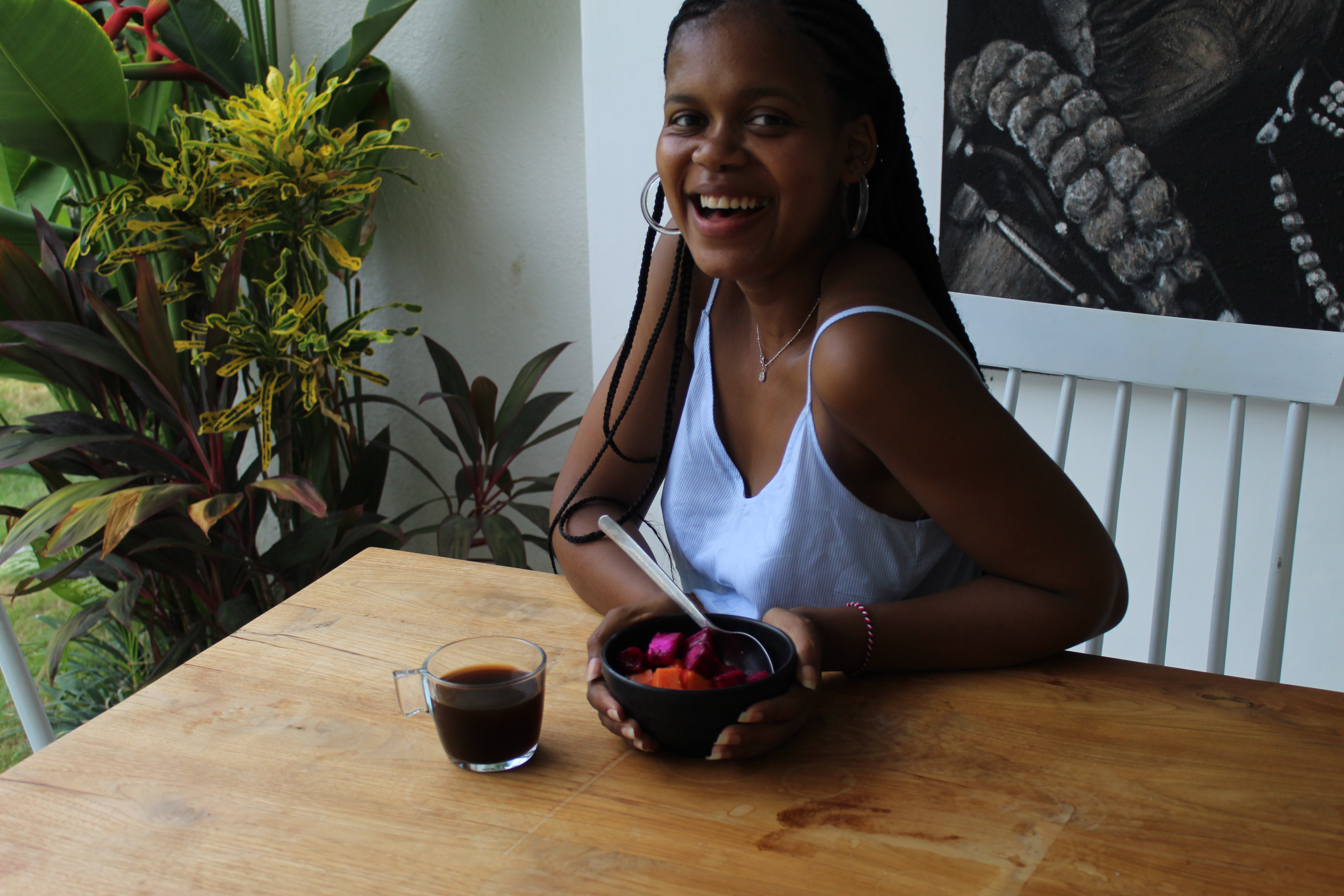girl smiling with coffee and fruit bowl on wooden table