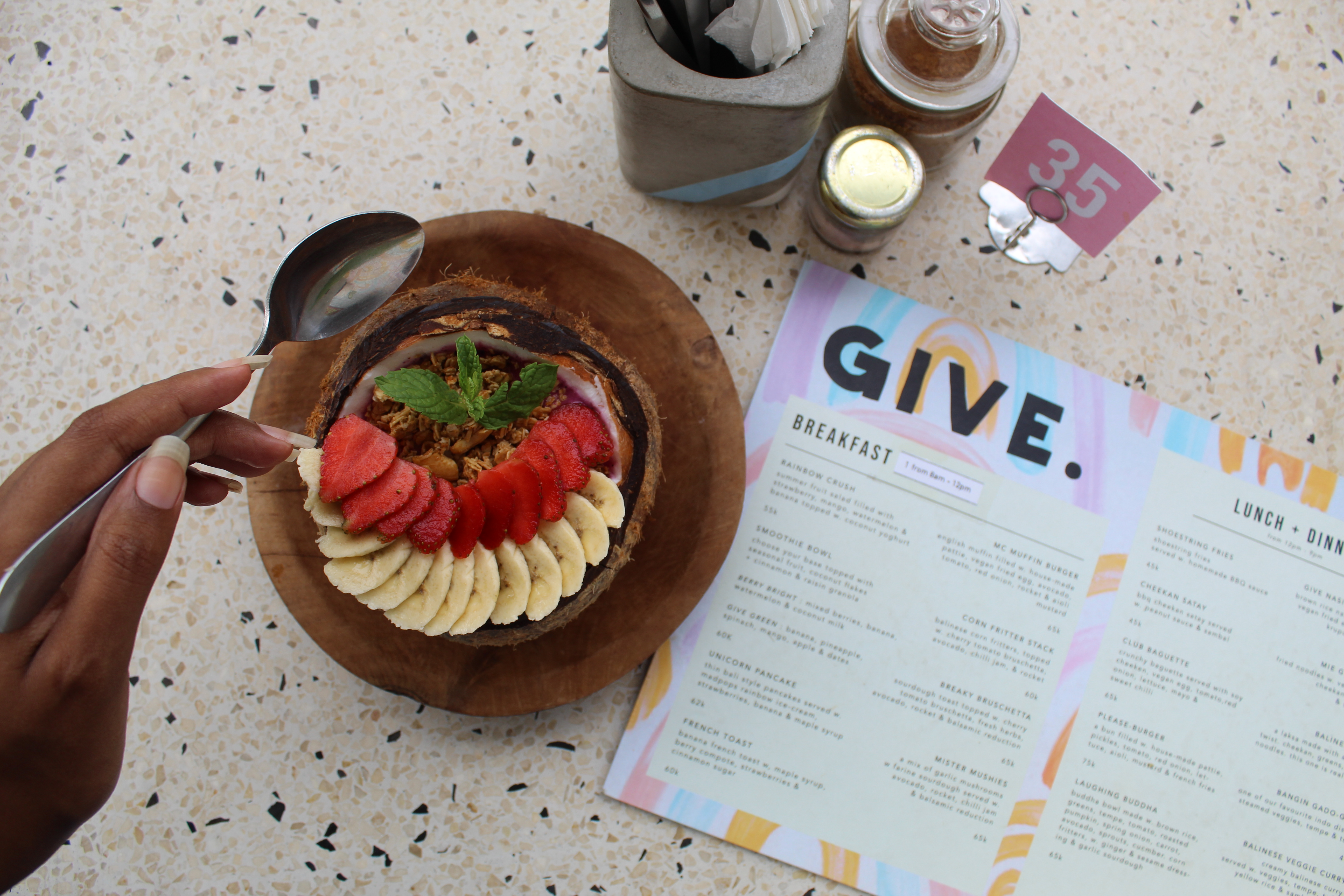 berry smoothie bowl with banana and strawberry and granola at give cafe in canguu bali
