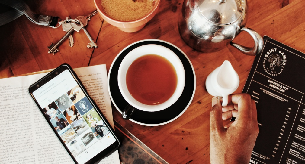flatlay with tea pot and tea and menu and keys and phone