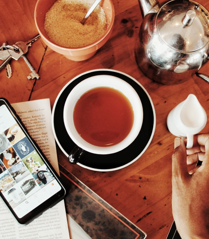 flatlay with tea pot and tea and menu and keys and phone