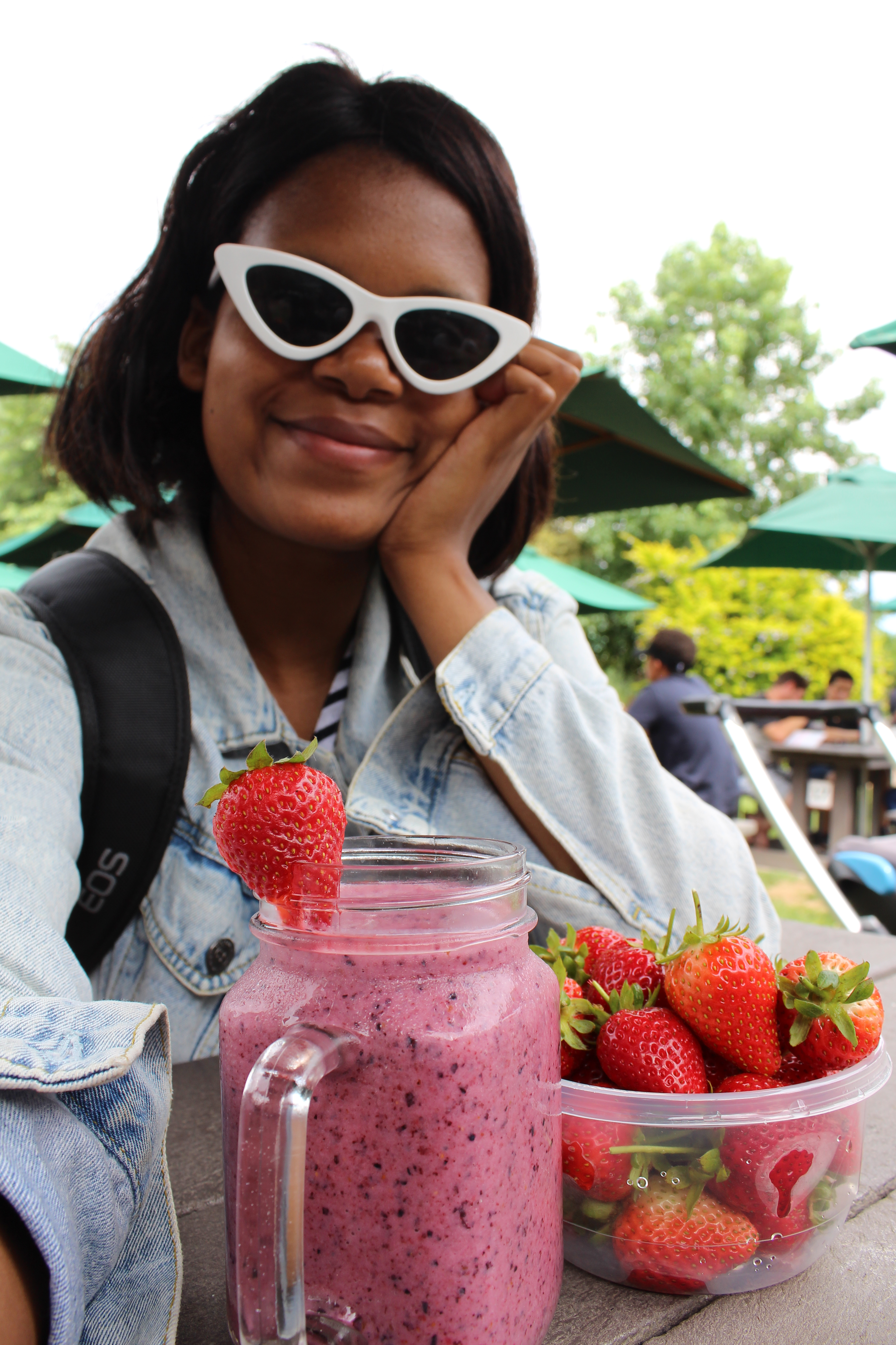 girl wearing sunglasses with strawberries and smoothie
