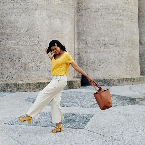 girl in yellow top with brown handbag for a fashion photoshoot